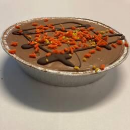 Mørk chokoladeis med appelsinsaft og pyntet med mørke chokoladestreger, orangechokolade og syltede appelsinskaller.